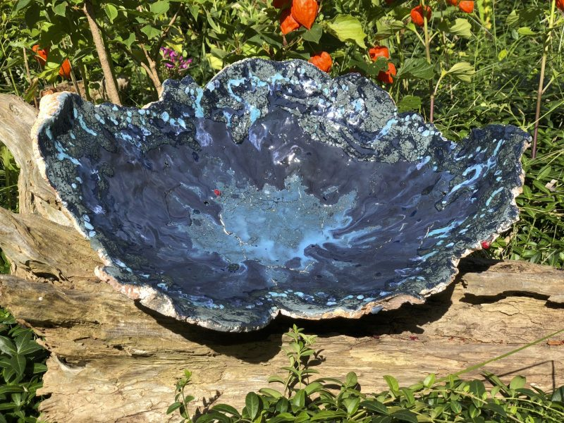 blue ceramic bowl on log