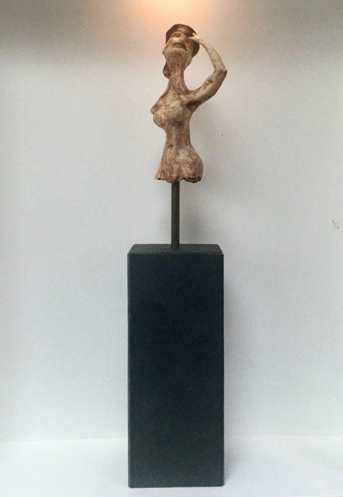 sculpture of woman's torso on slate  block