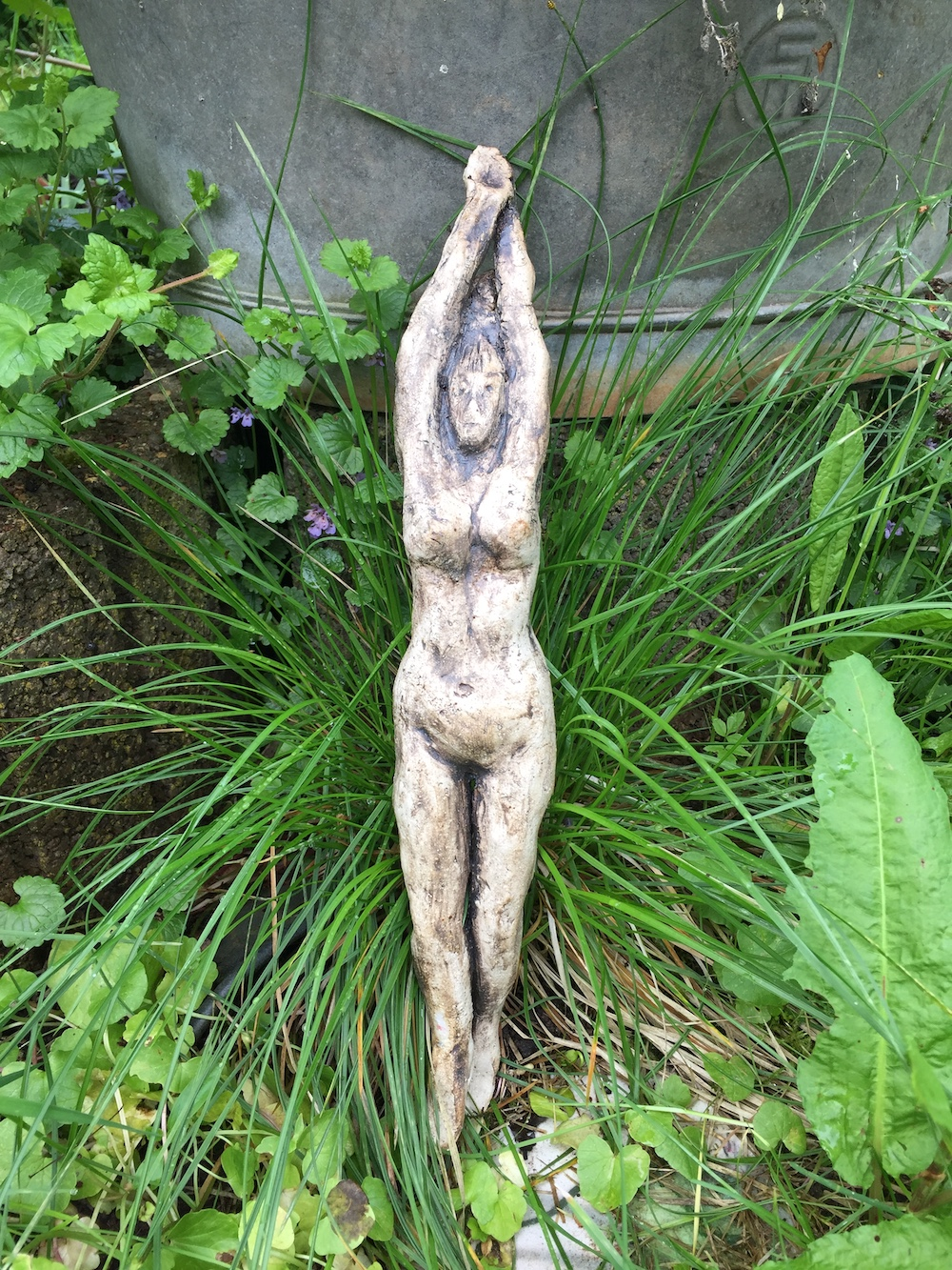 ceramic woman sculpture with hands up